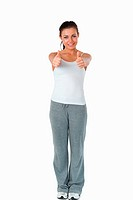 Sporty woman giving thumbs up against a white background