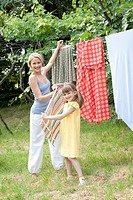 Mother and daughter doing the laundry                                                                                                                 ...