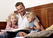 Father with daughters reading book