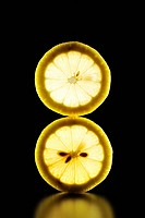 Two Lemon slice is illuminated black background