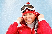 Pretty woman in goggles and winter sportswear looking at camera with smile