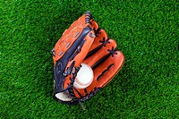 Photo of a baseball glove and ball on grass.
