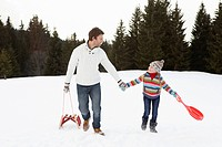 Young Father And Daughter Walking In Snow With Sleds