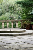 A low fountain next to some potted plants and stone railing