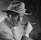 Man wearing hat holding cigarette, portrait