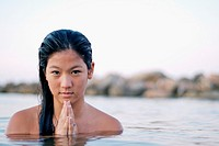 Cute young asian woman prays in water
