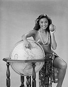 Woman in bikini standing beside globe and holding avocado, portrait