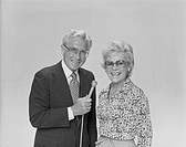 Senior couple holding microphone, smiling, portrait