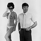 Nude woman wearing tie and sunglasses standing beside man