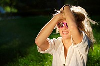 Cute young blonde woman in a park, wearing pink sunglasses