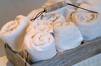 Rolls of bath towels in a tray