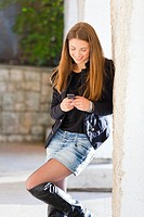 Attractive young woman is writting a message on a cellular phone