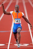 Young Male Athlete Raising Hand to Celebrate His Winning in Men´s 100 Meters