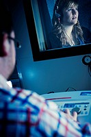 Scientist monitors a female patient aged 18_20 years wearing headphones during an audiology and deafness test in a sound booth.