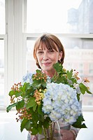 A mature woman holding a flower arrangement with Hydrangeas
