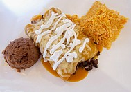 Mexican Steak enchiladas with rice and refried beans The enchiladas have melted cheesequeso and sour cream in a tomato based sauce