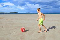 boy playing on sandy beach, Sutherland, Scotland