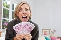 Excited woman holding 500 Euro notes