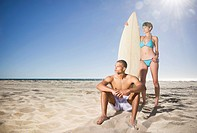 Mixed race couple on beach with surfboard