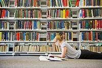 Caucasian woman studying on floor of library