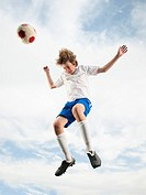 Caucasian teenager heading soccer ball in mid_air