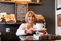 Woman serving coffee in cafe