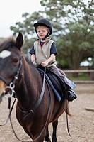 Boy riding horse in yard