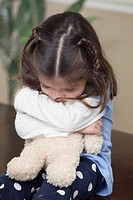 Young girl hugging teddy bear