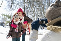Father taking picture of daughters in the snow with digital camera