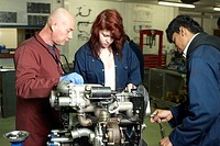 Teacher helping student with car engine