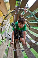 Boy playing in wooden tunnel