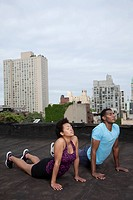 African American couple practicing yoga on rooftop