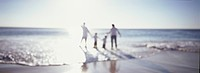 Family holding hands and wading in ocean at beach