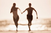 Couple in bathing suits holding hands and running on beach