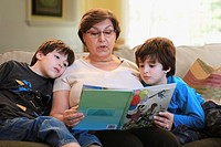 Grandmother reading book to grandsons