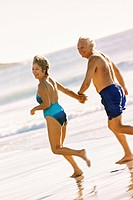 Smiling couple in bathing suits holding hands and walking on beach together