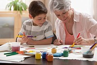 Caucasian grandmother and grandson painting together