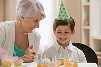 Caucasian grandmother and grandson sitting with birthday cupcakes