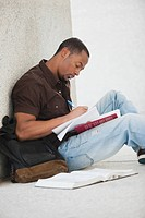 Black college student doing homework outdoor