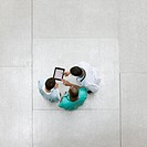 Doctors using digital tablet together in lobby