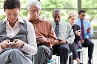 Business people sitting in chairs text messaging on cell phones