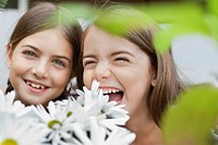 Grinning girls holding flowers