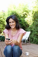 Woman sitting on patio holding cell phone