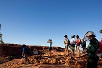 Australia, Northern Territory, Watarrka National Park, Group of hikers rests at top of Kings Canyon along cliff´s edge on summer morning