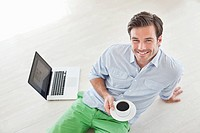 Smiling man sitting on floor with coffee and laptop
