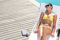 Woman laying on lounge chair sunbathing