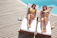 Friends laying on lounge chairs sunbathing near swimming pool