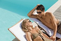 Couple laying on lounge chairs near swimming pool