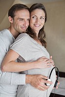 Man holding headphone to pregnant wife's stomach