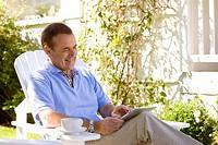 Man sitting in backyard using digital tablet